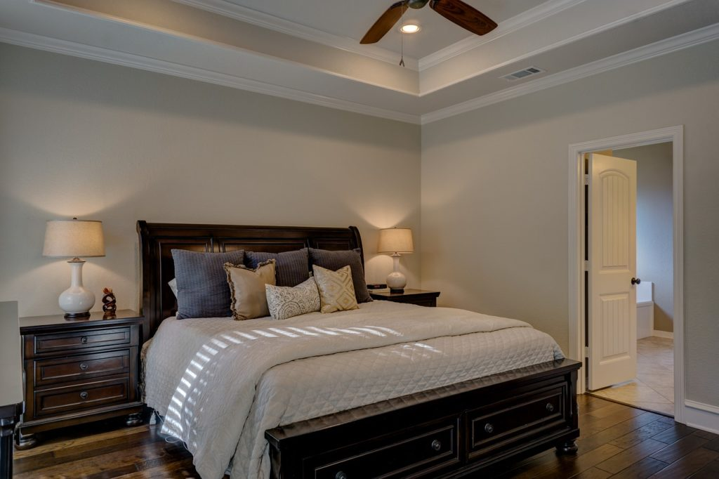A traditional bedroom with ceiling fan, spot lights and two nice table lamps