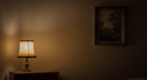 A table lamp and a poorly lit painting on a wall