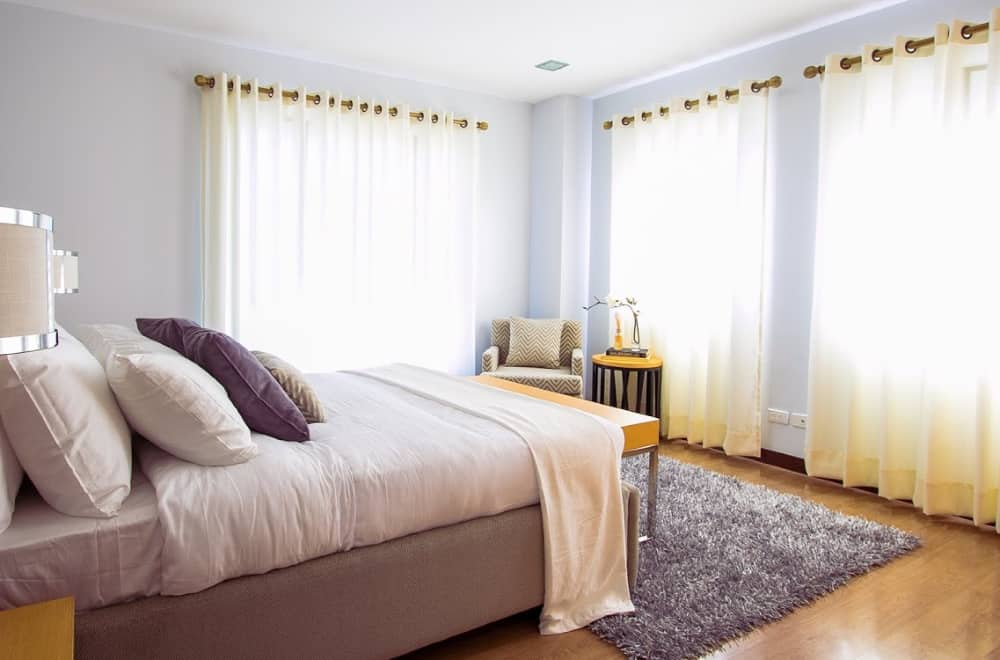A bedroom with long curtains
