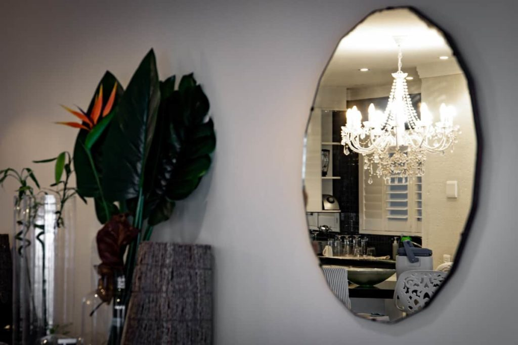 Oval wall mirror reflecting a chandelier is an affordable home improvement