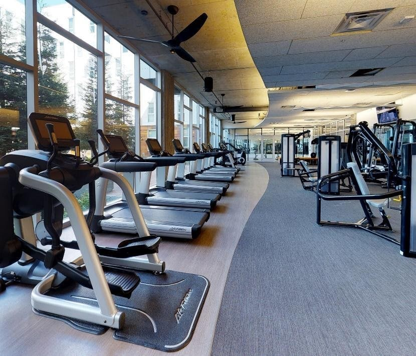 A view of a gym with treadmills and other exercise equipment under specific lighting