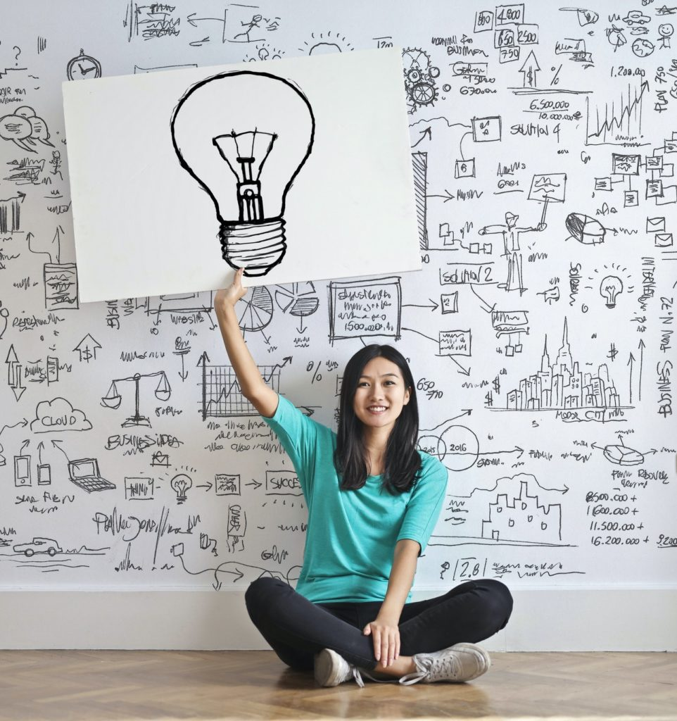 a girl holding an image of a lightbulb and thinking about energy-saving lighting solutions