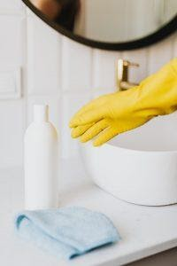 A hand in cleaning glove reaching for a white bottle