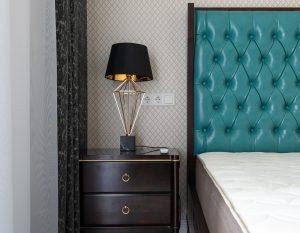 a lovely black table lamp next to the bed