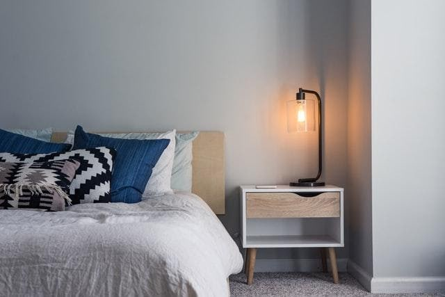 A bed, nightstand, and a bedside lamp