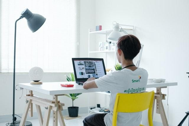 A child sitting on a yellow chair in front of a laptop