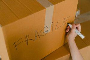 A person writing 'fragile' on a box